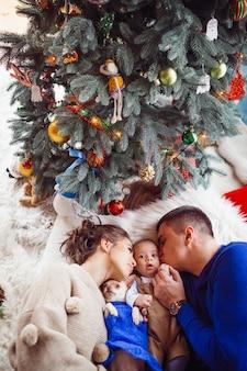 De moeder, vader, hond en baby liggen op de grond in de buurt van de kerstboom