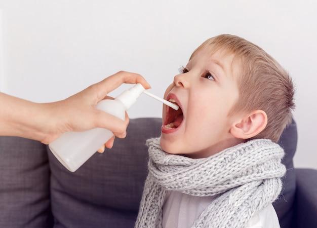 De moeder van een kleine jongen gebruikt een helende spray voor zijn keel. ziek kind bevriest verpakt in een sjaal. geneesmiddel tegen hoest.