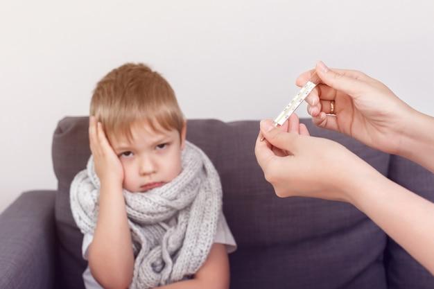 De moeder van een kleine jongen toont een thermometer met een temperatuur. ziek kind bevriest verpakt in een sjaal. griepseizoen.