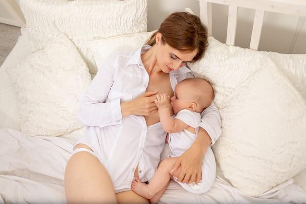 De moeder voedt de borst van de baby op het bed, het concept van babyvoeding voor het hele gezin