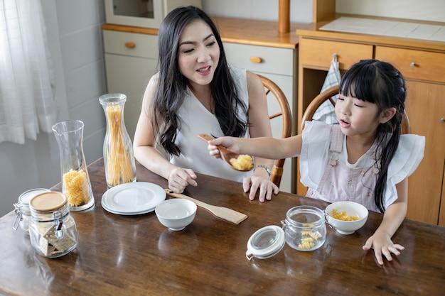 De moeder zit bekijkend de dochter die in de keuken speelt.