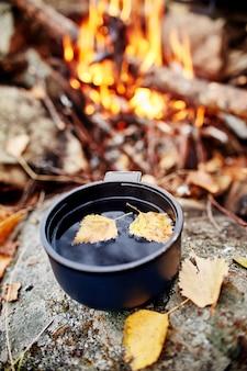 De mok hete thee is de herfst in een bos in goudgeel gebladerte. de herfst kwam, magische sfeer. gele bladeren die in de thee drijven