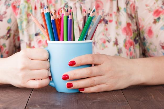 De mok van de vrouwengreep met velen kleurpotlood