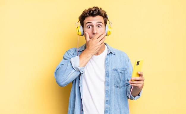 De mond bedekken met handen met een geschokte, verbaasde uitdrukking, een geheim bewaren of oeps zeggen. koptelefoon en smartphone concept