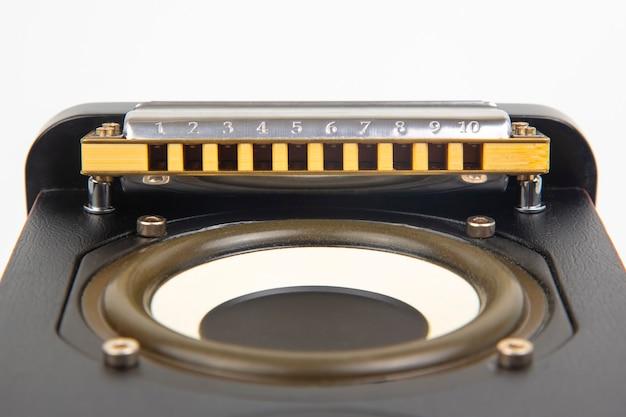 De mondharmonica ligt op de luidspreker. klassiek muzikaal blaasinstrument.