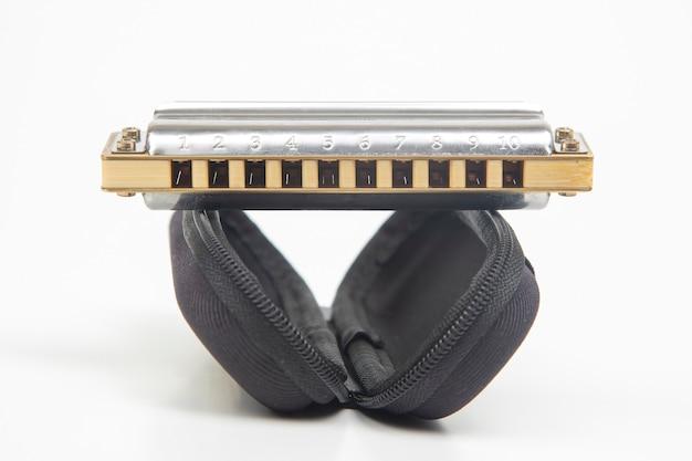 De mondharmonica ligt op een koffer op een witte achtergrond. klassiek muzikaal blaasinstrument.