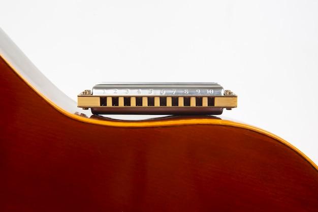 De mondharmonica rust op de body van een klassieke gitaar. klassiek muzikaal blaasinstrument.