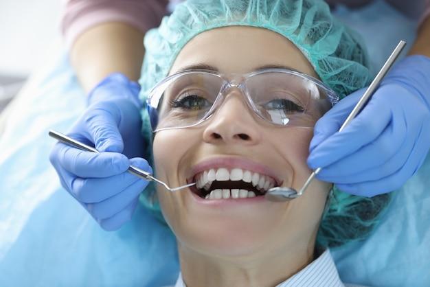 De mondholte van de vrouw wordt onderzocht op het kantoor van de tandarts