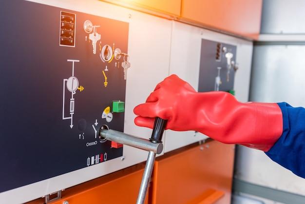 De monteur controleert de afwezigheid van geïnduceerde spanning op de hoogspanningscellen