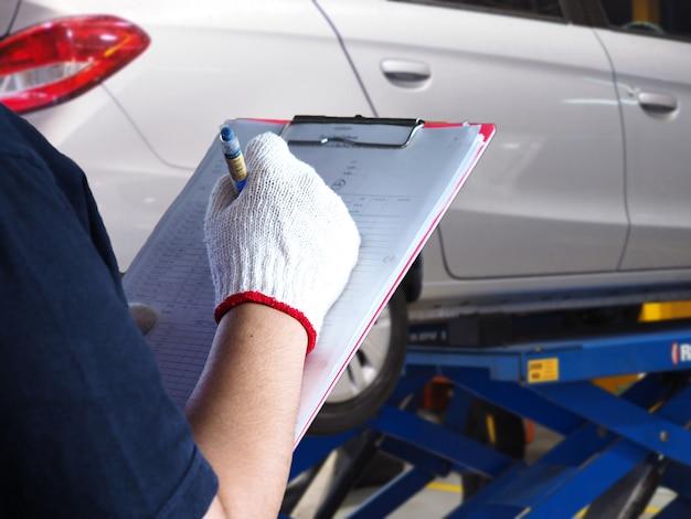 De monteur controleert de auto.