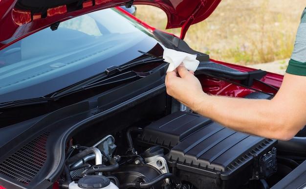 De monteur controleert het oliepeil in de auto, het concept van het probleem op de weg