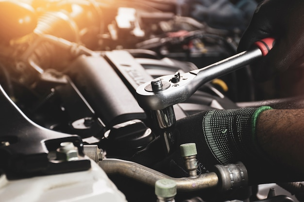De monteur hand die zwarte handschoenen draagt, zet de bout vast met de dopsleutel om de motor van de auto te repareren