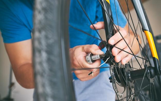 De monteur repareert de racefiets in zijn werkplaats