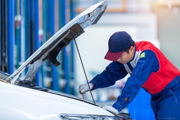 De monteur van de jonge mensenauto in een de dienstcentrum van de autoreparatie analyseert motorproblemen en controleert de motor. automonteur werken in auto reparatie service center.
