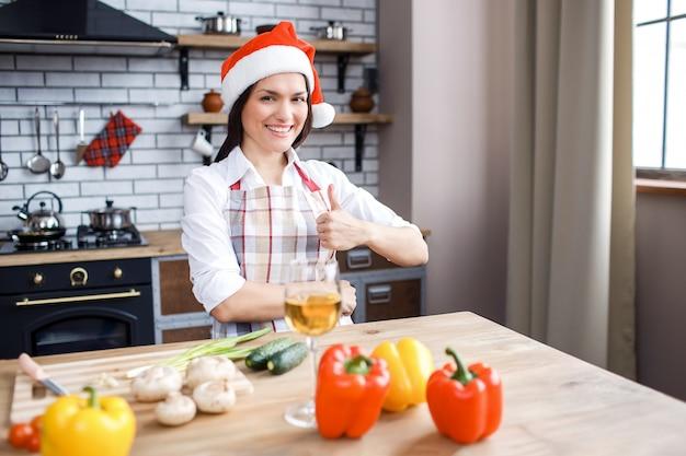 De mooie aantrekkelijke vrouw in rode hoedentribune in keuken en stelt op camera