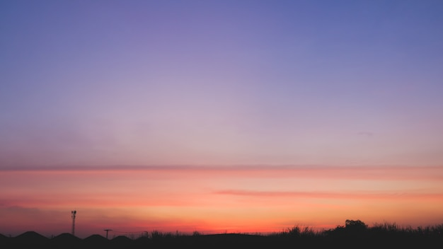 De mooie achtergrond van het zonsonderganglandschap in dramatisch concept. blauwe en oranje heldere hemeltoon en silhouetstad.