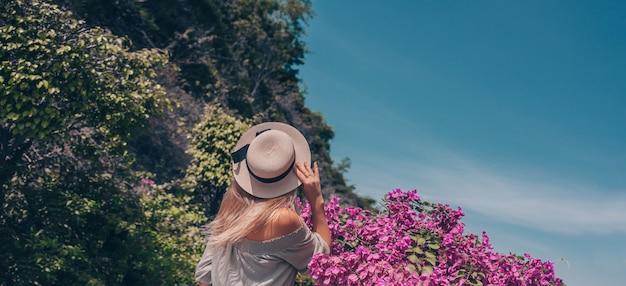 De mooie achtermening van de blondevrouw loopt en bewondert tropische landschappen bij het hotel van het paradijseiland in sanya, china. luxe vakantie banner. tropisch resort concept. azië reizen levensstijl toerist