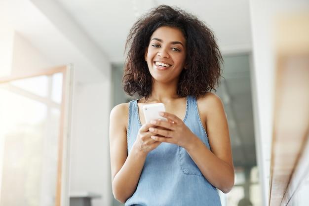 De mooie afrikaanse vrouw het glimlachen zitting van de holdingstelefoon in koffie.