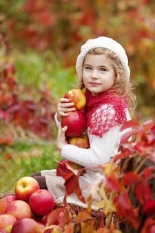 De mooie appelen van de meisjeholding in de de herfsttuin. . meisje het spelen in de boomgaard van de appelboom. peuter die vruchten eet bij herfstoogst. outdoor plezier voor kinderen. gezonde voeding