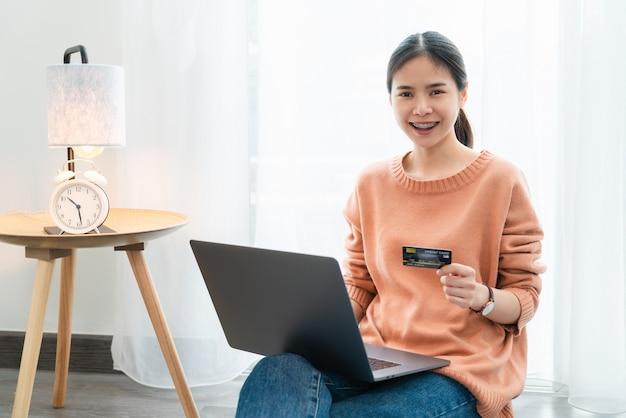 De mooie aziatische creditcard van de vrouwenholding en het gebruiken van digitale laptop met online winkelen