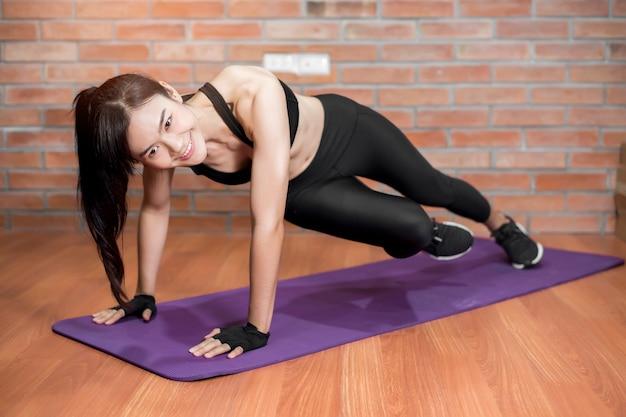 De mooie aziatische fitnessesvrouw is thuis oefening