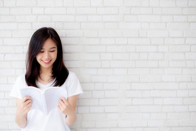 De mooie aziatische gelukkige vrouw opent het boek