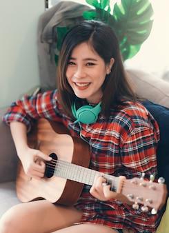 De mooie aziatische jonge vrouw het spelen gitaar thuis voor ontspant