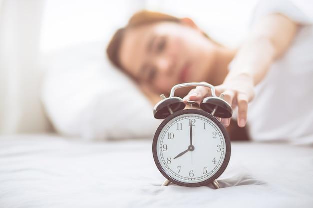 De mooie aziatische jonge vrouw schakelt wekker in goedemorgen uit