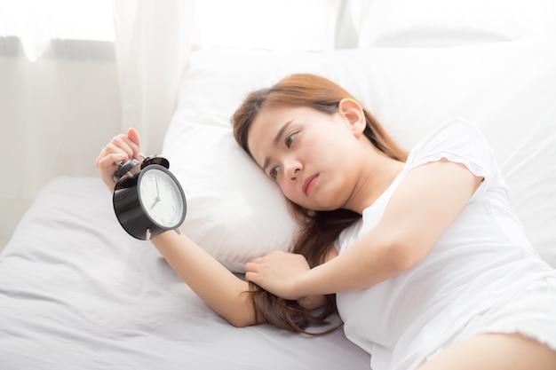 De mooie aziatische jonge vrouw schakelt wekker in goedemorgen uit.