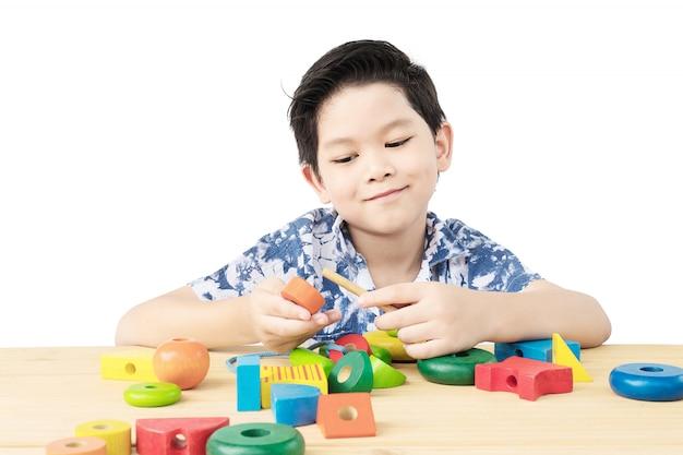 De mooie aziatische jongen is speel kleurrijk houtsnedestuk speelgoed