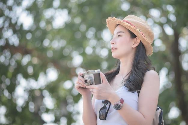 De mooie aziatische solo toeristenvrouw geniet van nemend foto door retro camera
