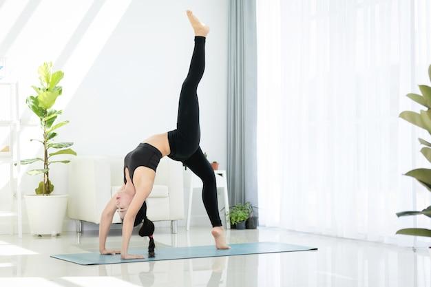 De mooie aziatische sportenvrouw voert thuis de oefeningen uit. yoga