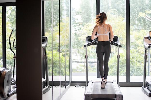 De mooie aziatische sportvrouw loopt op tredmolen in de gymnastiek