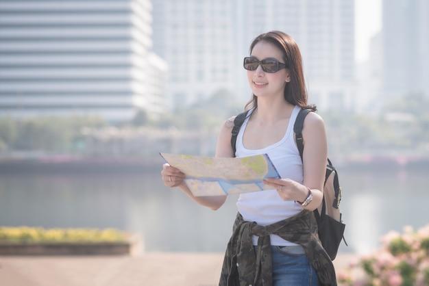 De mooie aziatische vrouw die van de solooerist de kaart bekijken die naar sightseeingsvlek zoeken.