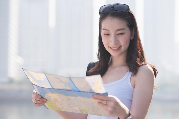 De mooie aziatische vrouw die van de solooerist de kaart bekijken die naar toeristen zoeken die vlek bezoeken.