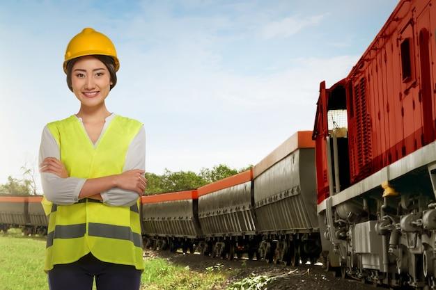 De mooie aziatische vrouw die van de spoorwegemployee naast goederentrein bevindt zich