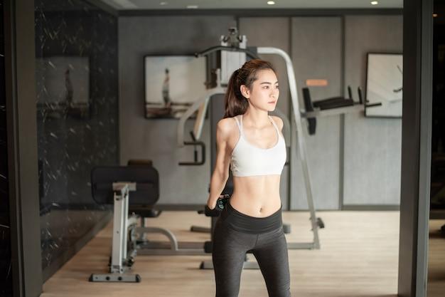 De mooie aziatische vrouw doet oefening in de gymnastiek