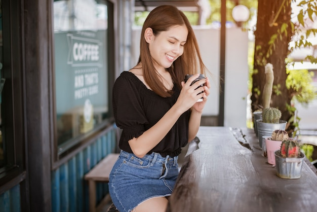 De mooie aziatische vrouw drinkt koffie