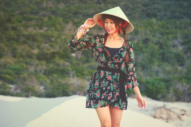 De mooie aziatische vrouw geniet van haar vakantie op wit zandduin in mui-ne, vietnam