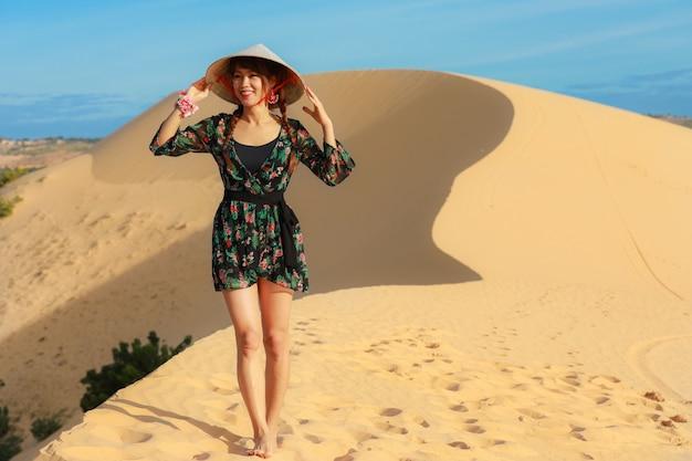 De mooie aziatische vrouw geniet van haar vakantie op wit zandduin in ne van mui, vietnam