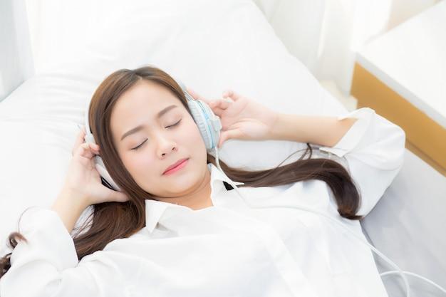 De mooie aziatische vrouw geniet van luistermuziek met hoofdtelefoon