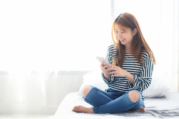De mooie aziatische vrouw het glimlachen zitting ontspant op het bed
