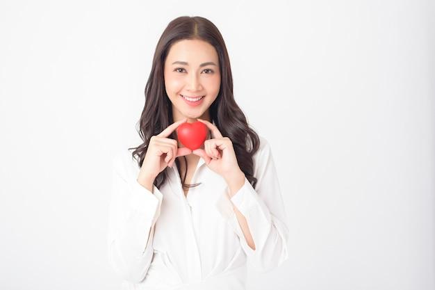 De mooie aziatische vrouw houdt rood hart (gezondheidszorgconcept)