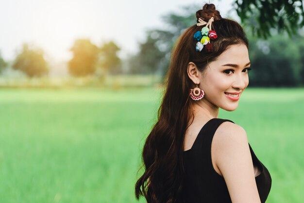 De mooie aziatische vrouw in lokale kleding die bevindt zich en geniet van natuurlijk op bamboebrug in padieveld