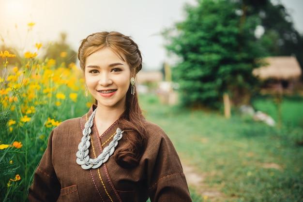 De mooie aziatische vrouw in lokale kledingszitting op grond en geniet van natuurlijk op padieveld