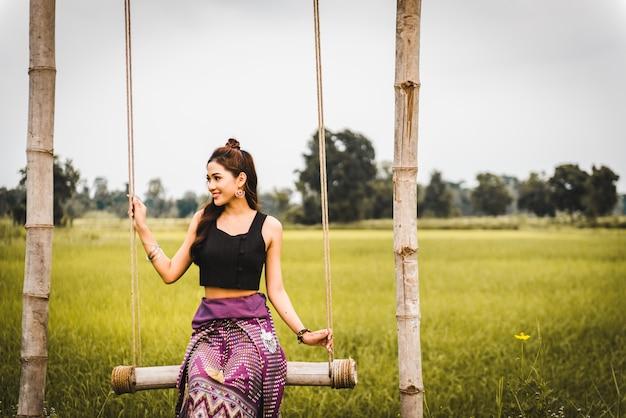 De mooie aziatische vrouw in lokale kledingszitting op schommeling en geniet van natuurlijk op bamboebrug in padieveld