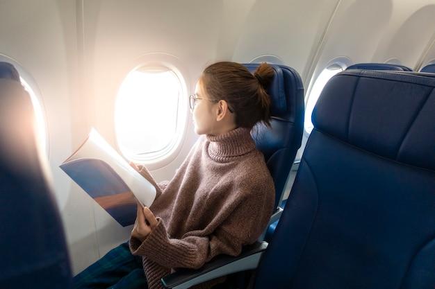 De mooie aziatische vrouw leest tijdschrift in vliegtuig