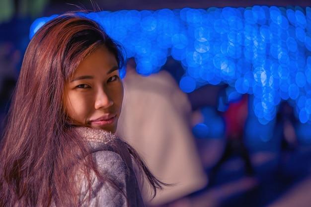 De mooie aziatische vrouw loopt openlucht met het licht van nieuwjaarkerstmis op de achtergrond