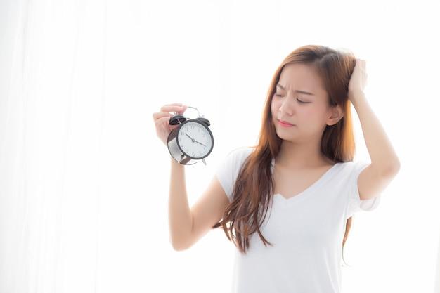 De mooie aziatische vrouw ontwaakt in ochtend geërgerde wekker