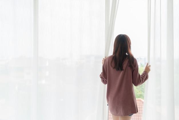 De mooie aziatische vrouw opent het gordijn in de ochtend